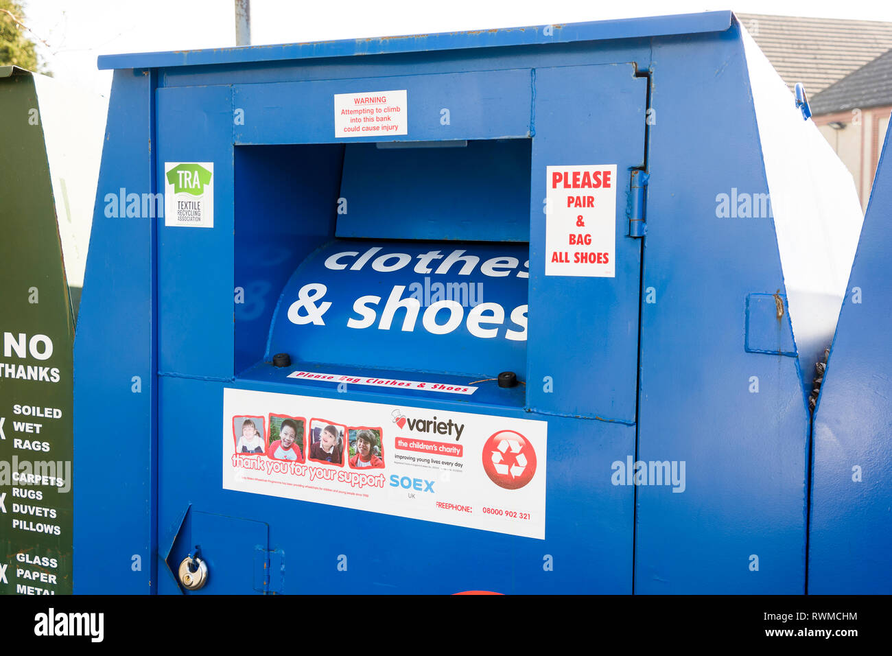 Distinctive large blue metal receptacle for donations of surplus clean and serviceable clothing and shoes for recycling with proceeds going to sponsor - Stock Image