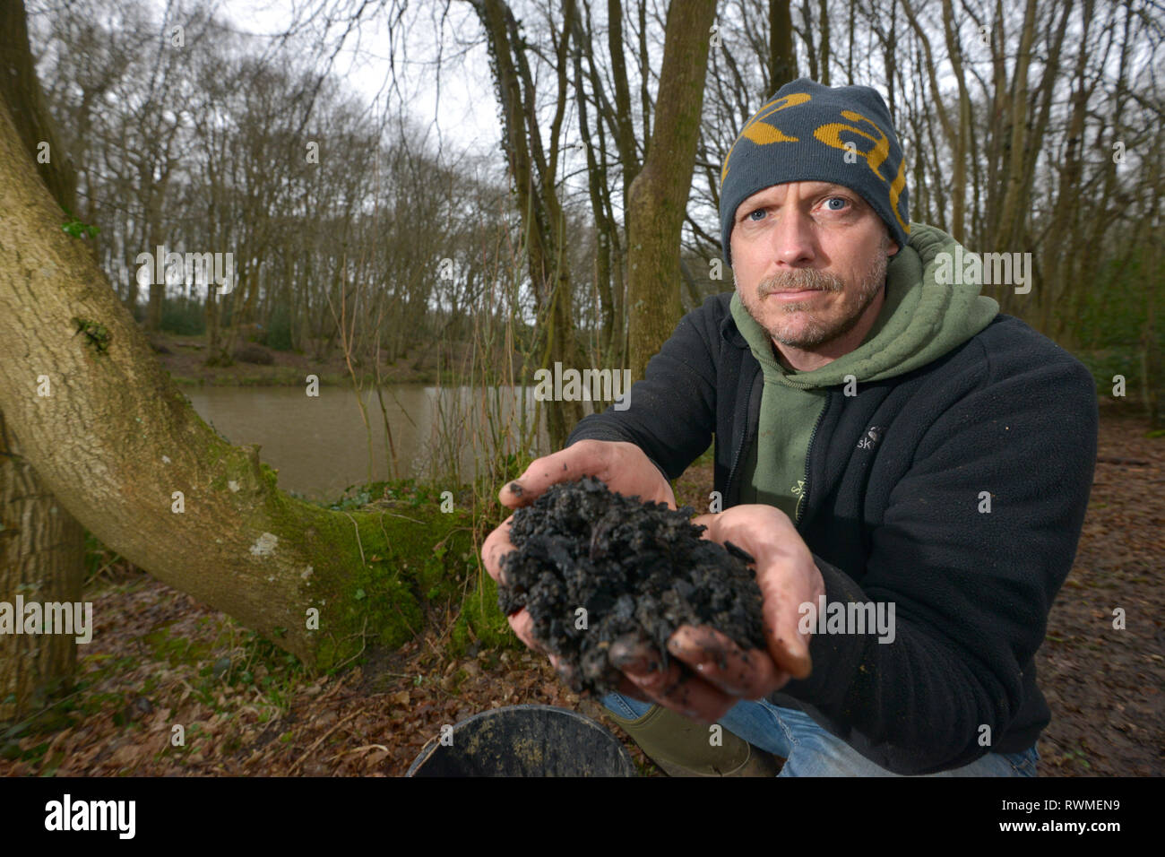 Phil Greenwood of Sacred Earth, Horam, East Sussex, with biochar - a natural soil enrichment that could help suppress ash dieback disease. - Stock Image