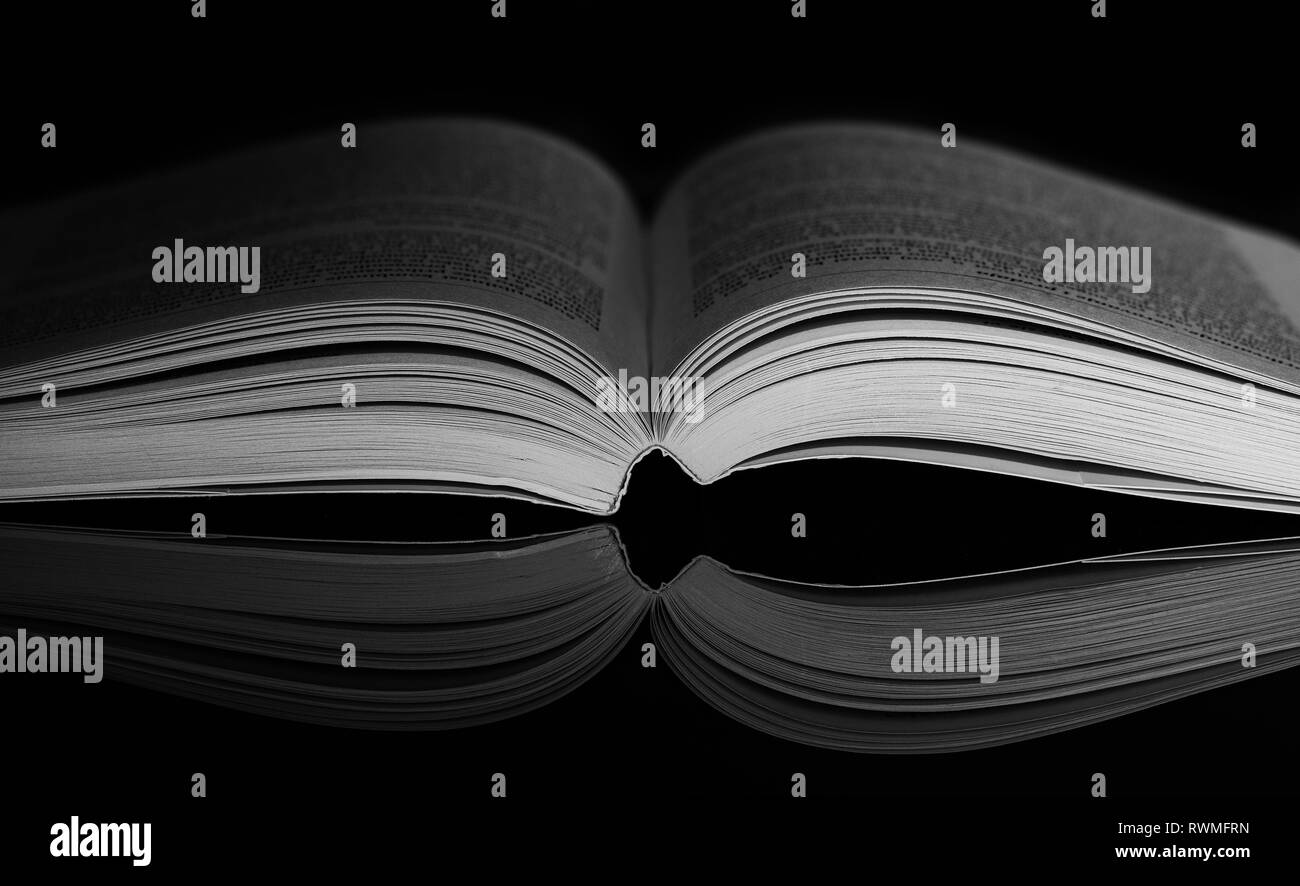 Opened book on black background with mirror reflection. Dramatic side light on book. Low key photography - Stock Image
