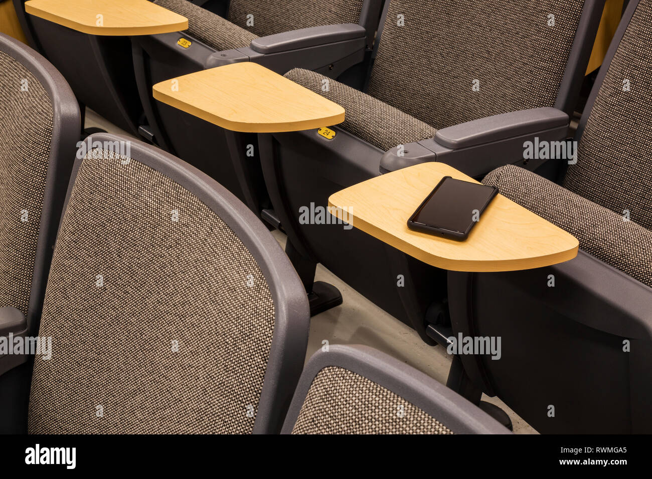 Cell phone on a student's desk in an empty college lecture hall; Connecticut, United States of America - Stock Image