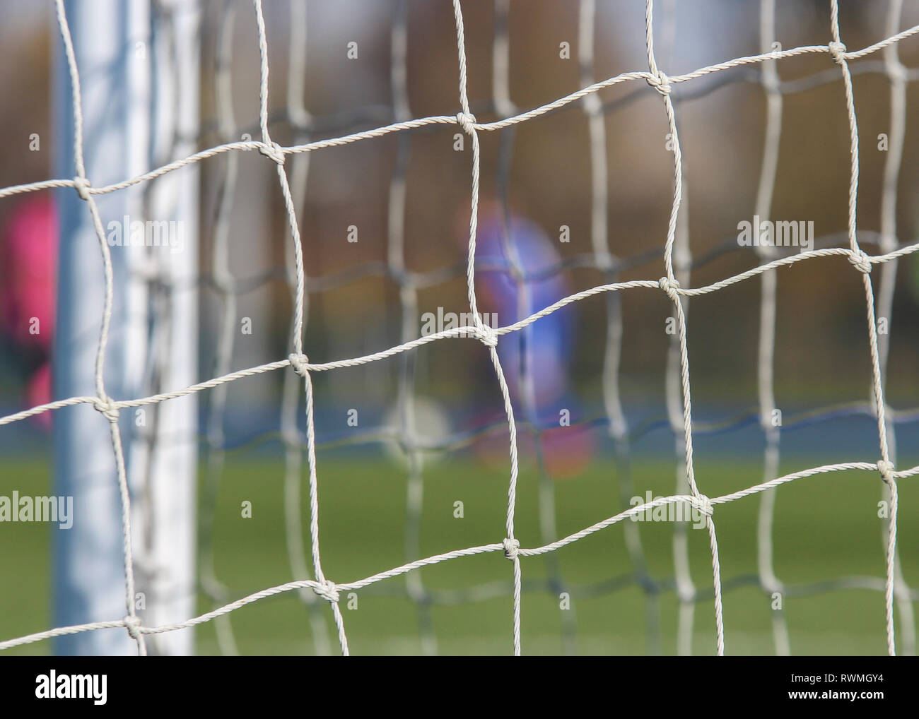 Football player with ball through net of the goal. - Stock Image