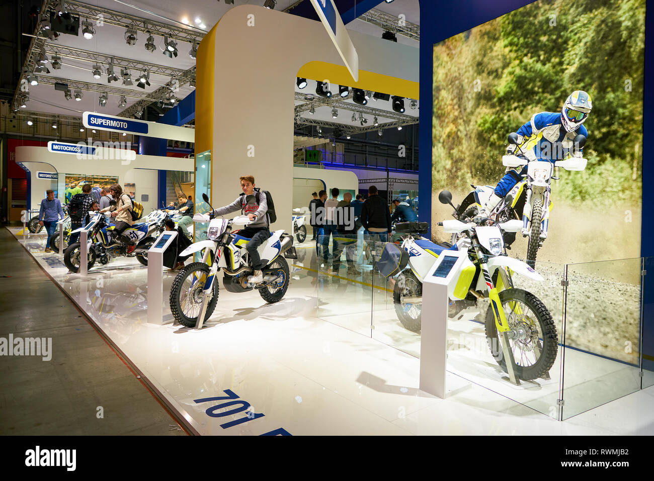 MILAN, ITALY - NOVEMBER 11, 2017: visitors try out a motorcycle at the EICMA 2017 - 75th International Motorcycle Exhibition. - Stock Image