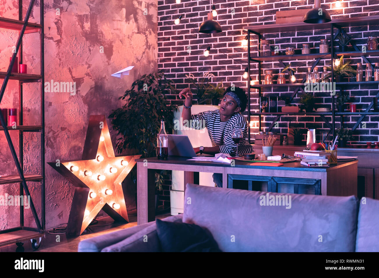 Young man standing near the table with a laptop and flying paper planes instead of working. Stock Photo