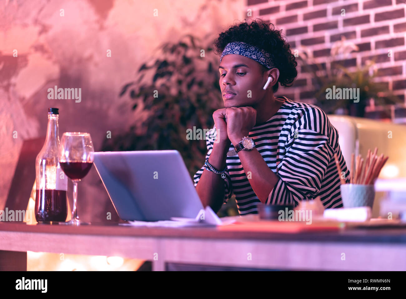 Young man adjusting earbuds to better work with portable computer while drinking wine. - Stock Image