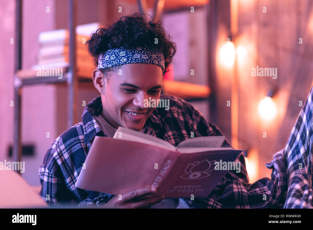 Boy surprisingly candidly smiling to romantic story he reading in his book. - Stock Image