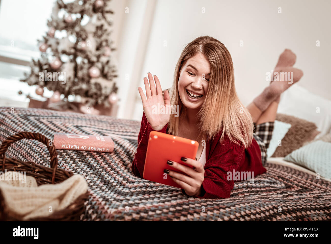 Coquettish young girl using tablet for video connection - Stock Image