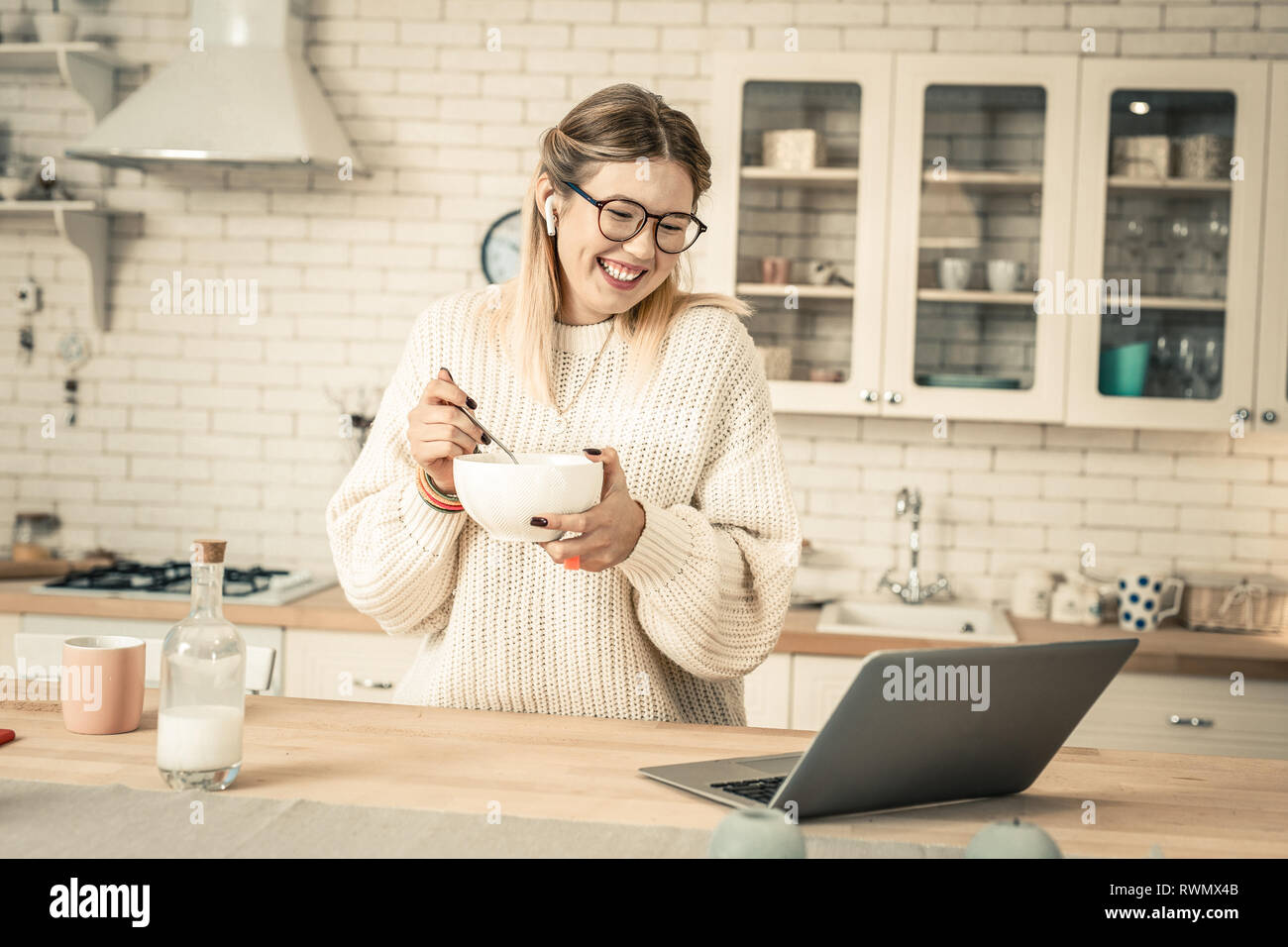 Cheerful attractive woman with wide smile carrying bowl with breakfast - Stock Image