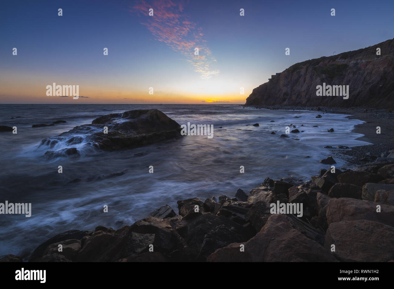 Long exposure photo of striking tall cliffs and waves crashing into a large rock formation after sunset, Dana Point, California - Stock Image