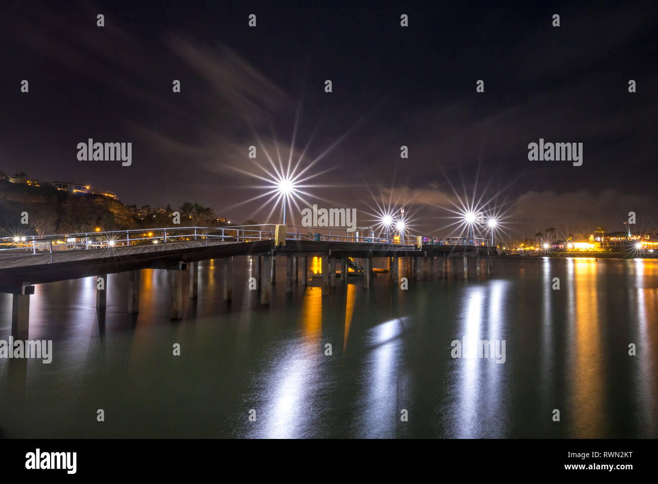 Long exposure photo of Dana Point Pier at night with lights from Dana Point Harbor reflecting in the water, Dana Point, California - Stock Image