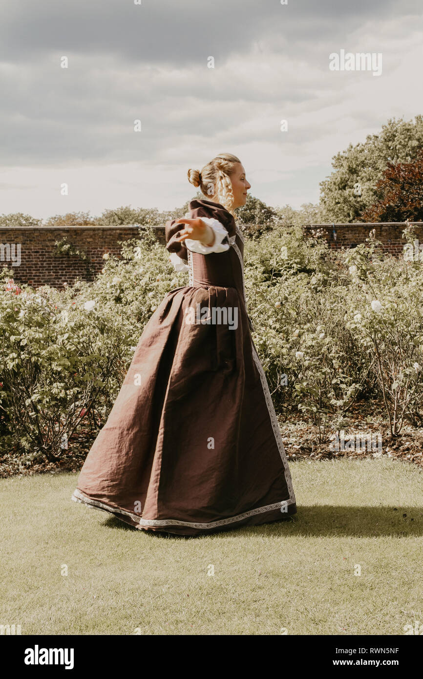 Portrait of a beautiful young woman in ornate historical dress- her clothes are fine, she is in the rose garden at Hampton Court Palace. - Stock Image