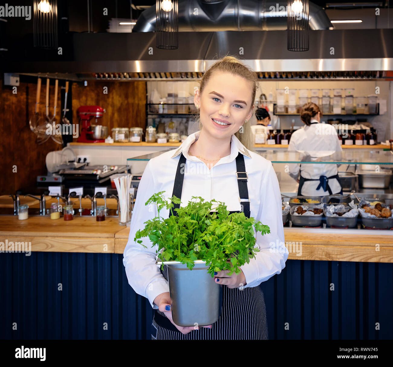 Smiling Young Woman holding fresh parsley. Employee standing in front of the Restaurant counter and employees working in background - Stock Image