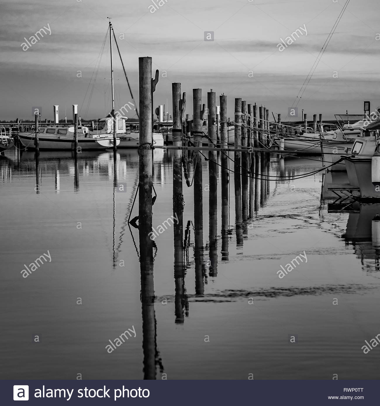 A quiet evening at Lynaes harbor, Denmark, with poles reflecting in the water - Stock Image