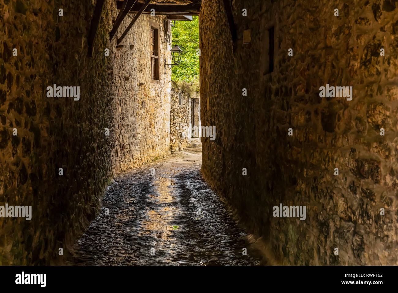 Narrow pathway between stone walls of buildings; Santillana del Mar, Cantabria, Spain - Stock Image