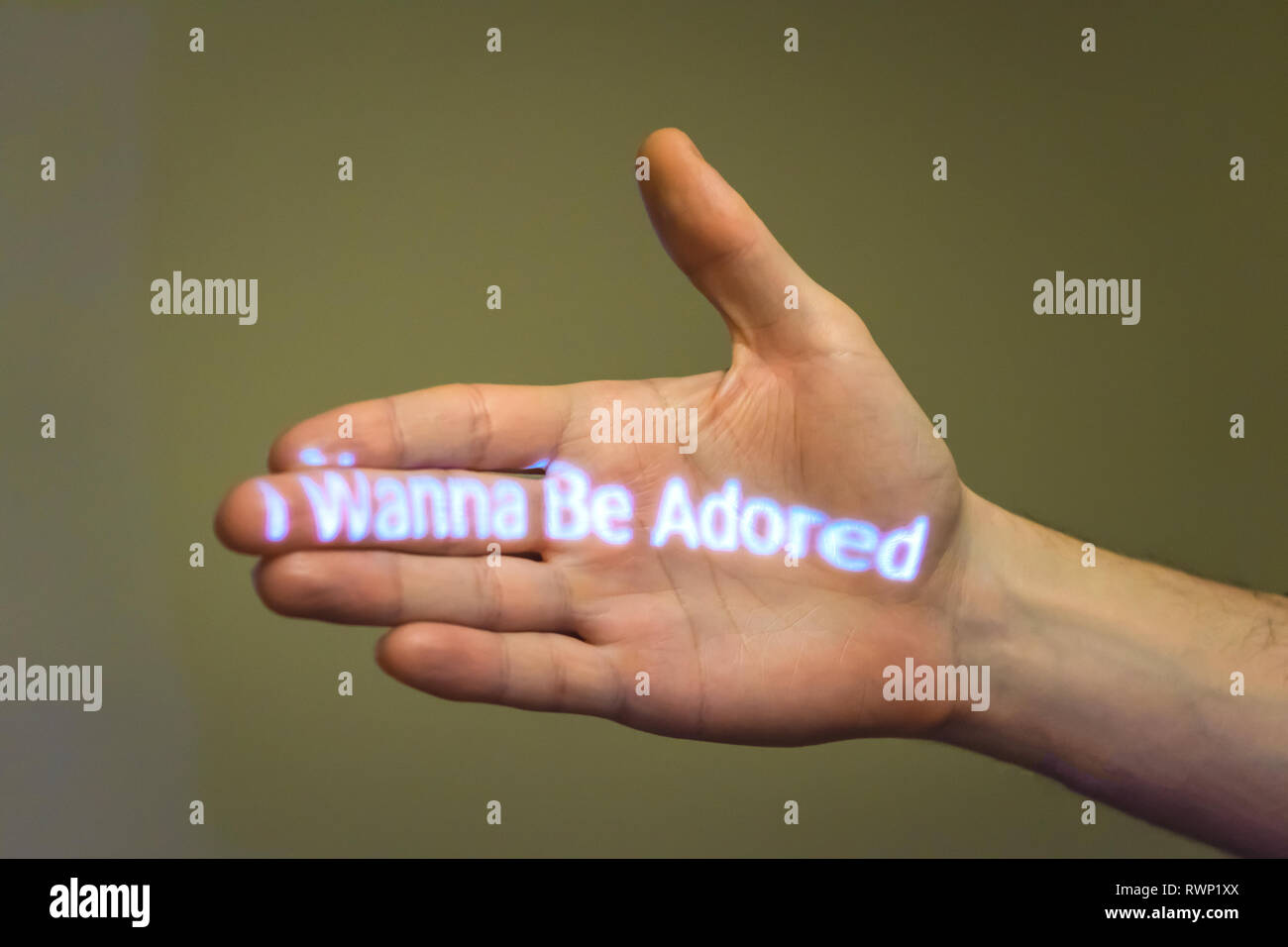 'I wanna be adored' statement projected on to a male hand - Stock Image