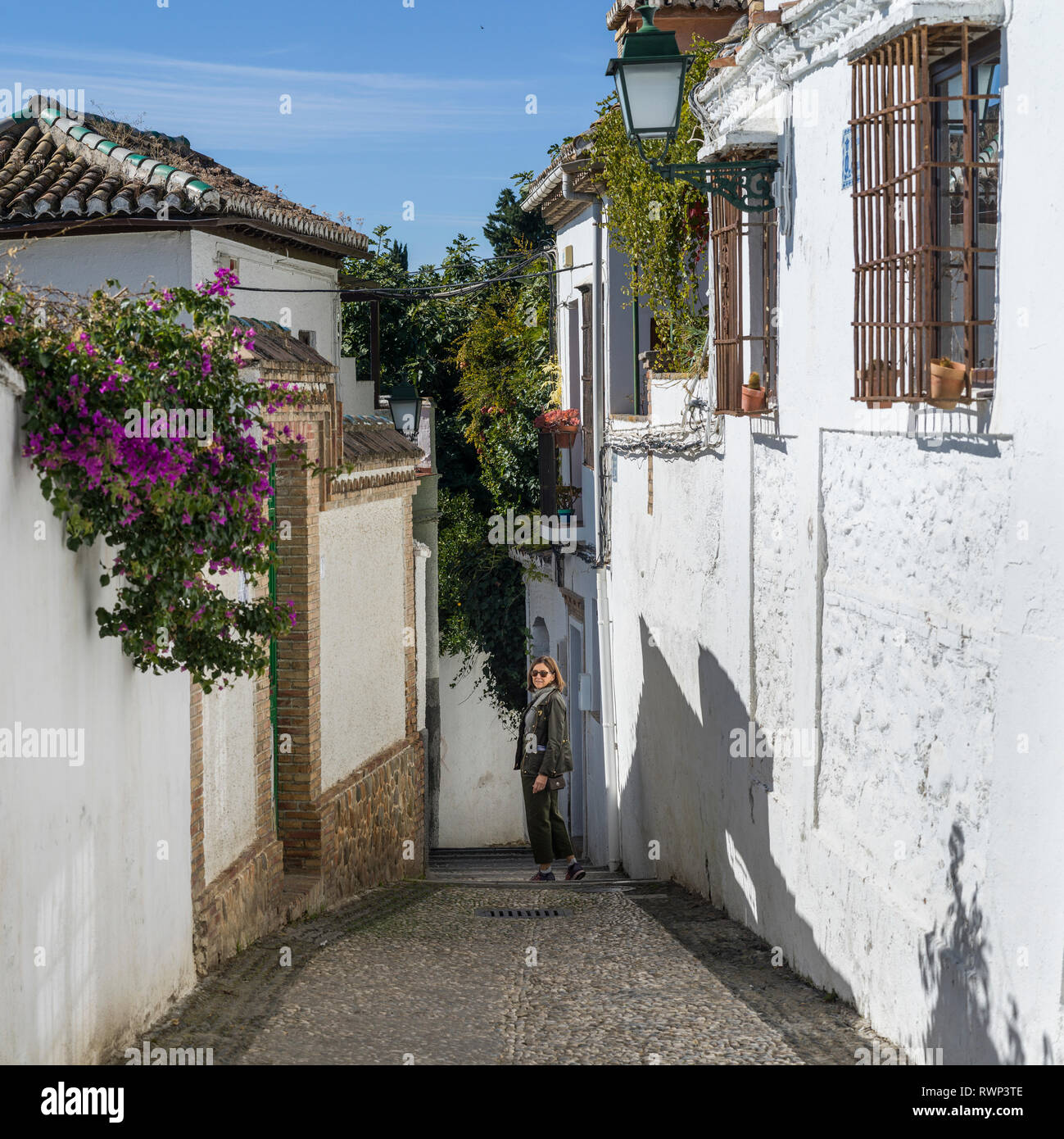 A woman stands posing on a narrow walkway between the whitewash walls of houses; Granada, Spain - Stock Image