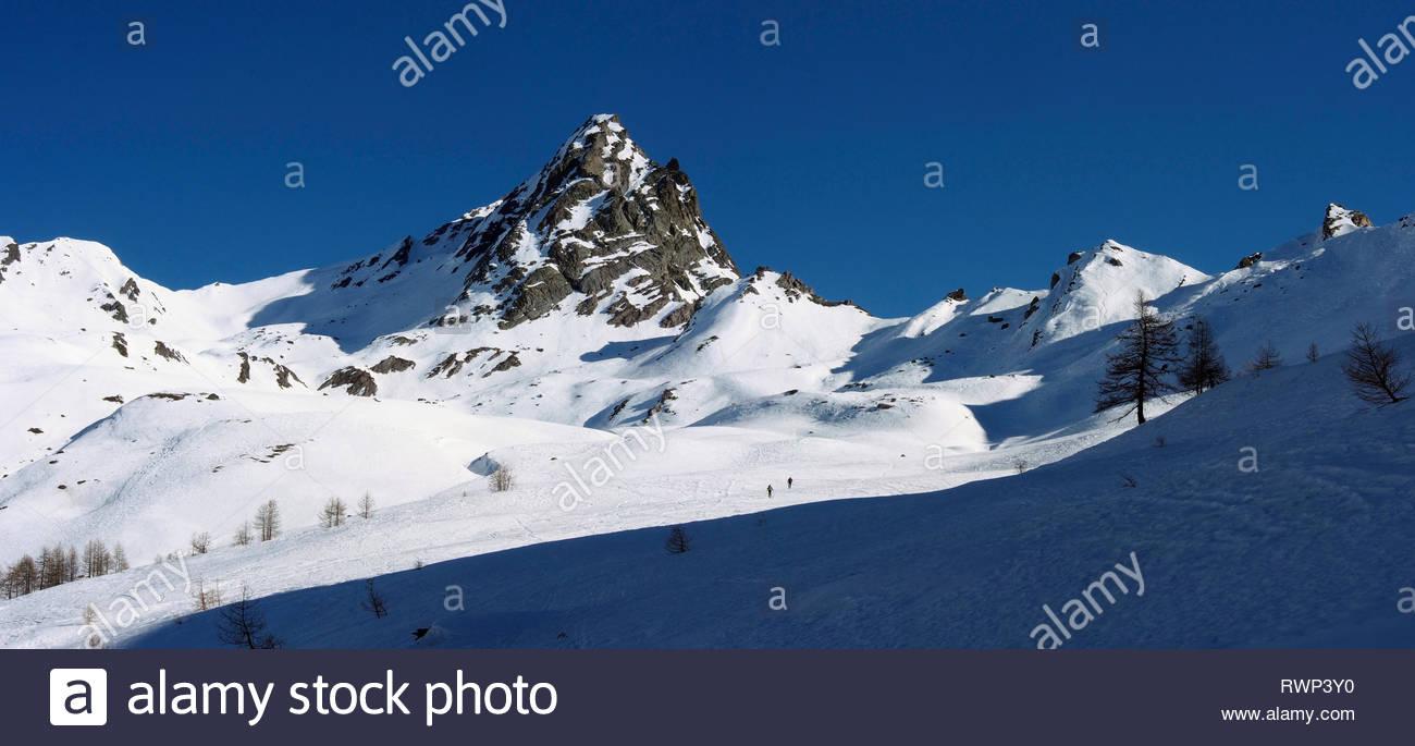 Ski mountaineers below Bric Bouchet, Parc regional du Queyras, French Alps - Stock Image