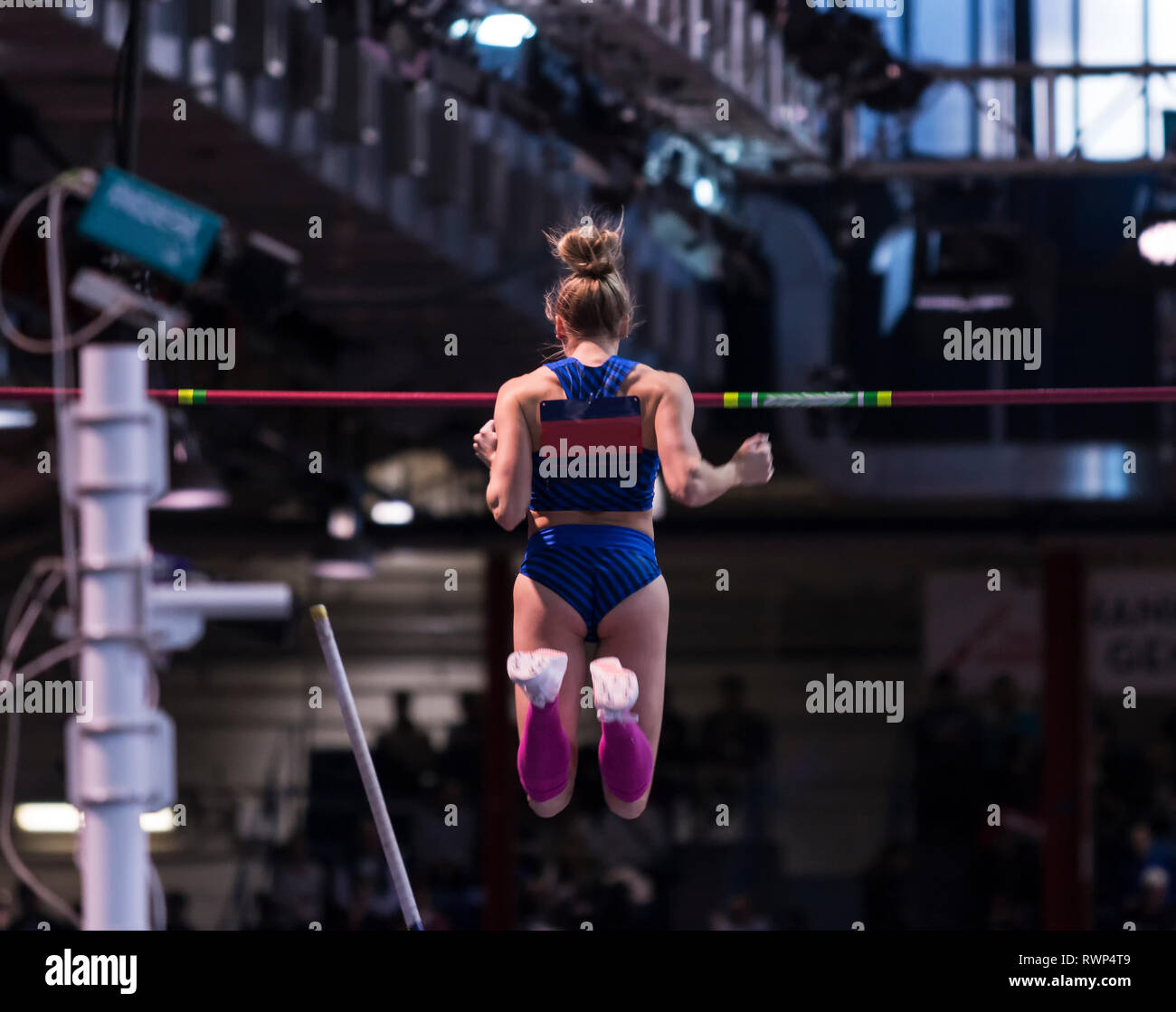 A female pole vaulter falling in the air after clearing a height in a pole vault competition, from behind. - Stock Image