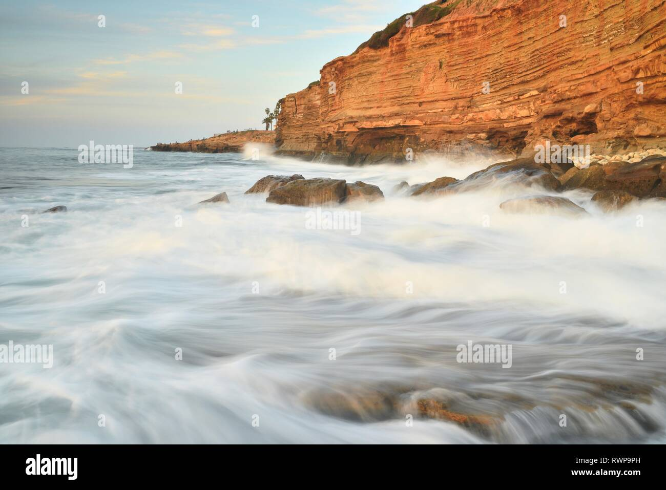 Crashing waves over rocks, with water motion of surf, gold glow on rugged cliffs at Sunset Cliffs Natural Park, Point Loma, San Diego, California, USA Stock Photo