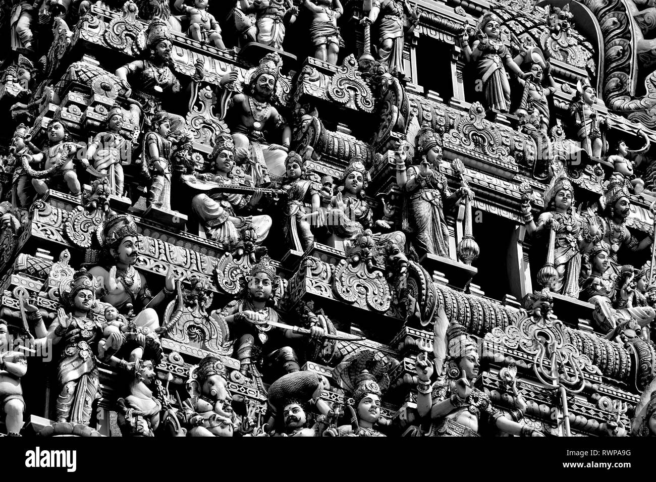 Perspective view of ancient temple tower with stone statues depicting Indian Hindu Gods and Deities on the exterior of an old temple in Little India, Stock Photo