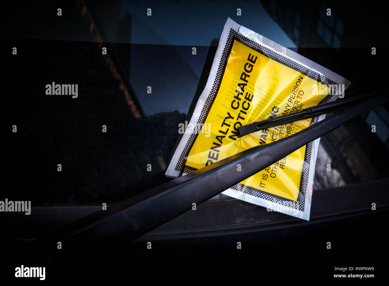 Yellow windscreen sticker containing a Fixed Penalty Parking Charge Notice for illegal parking fine fee stuck onto a car windscreen. - Stock Image