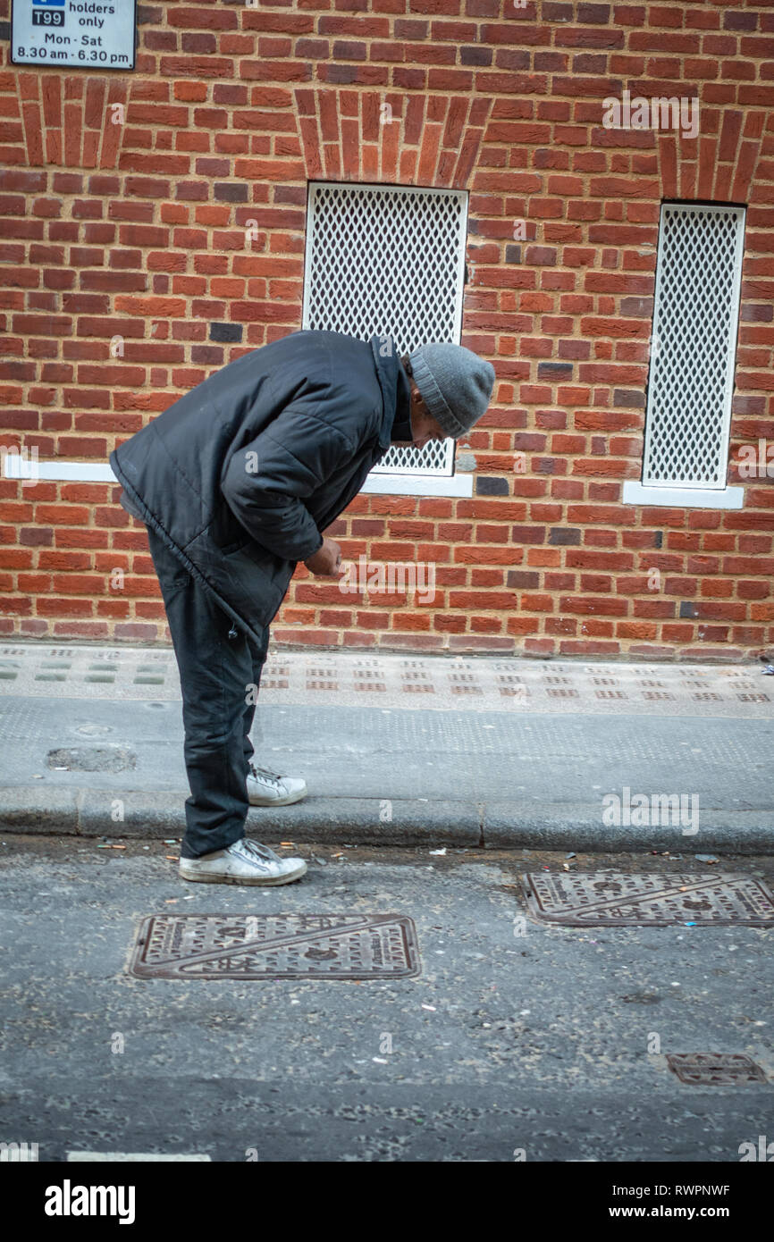 Older man bending down searching the street gutter for used and discarded cigarette ends - Stock Image