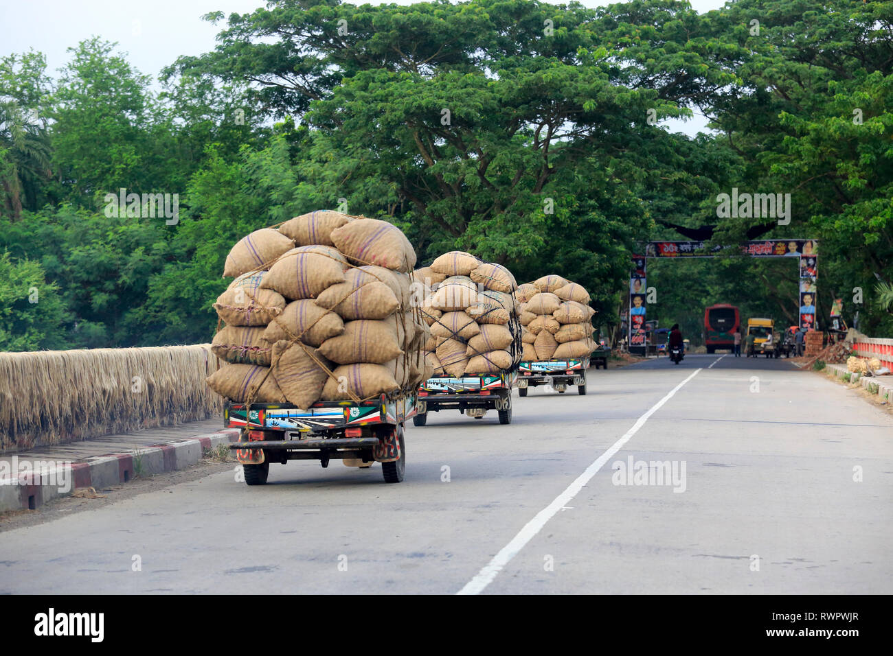 Sacks of onion loaded on the locally assembled tricycle called Nachimon on the Faridpur-Gopalganj highway. Faridpur, Bangladesh. - Stock Image