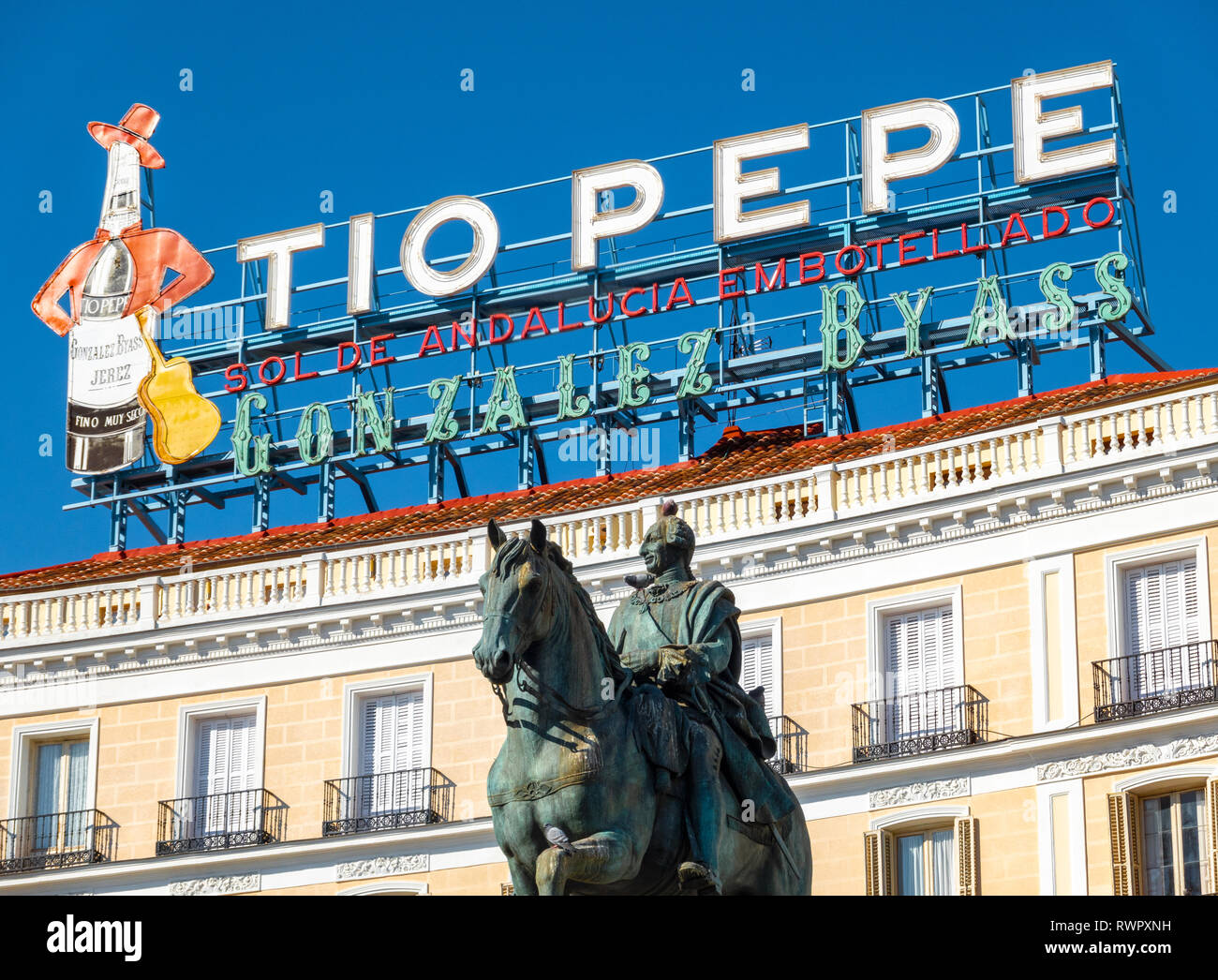 The landmark Tio Pepe sign above Puerta del Sol Square with the statue of Carlos III Charles III of Spain in Madrid Stock Photo