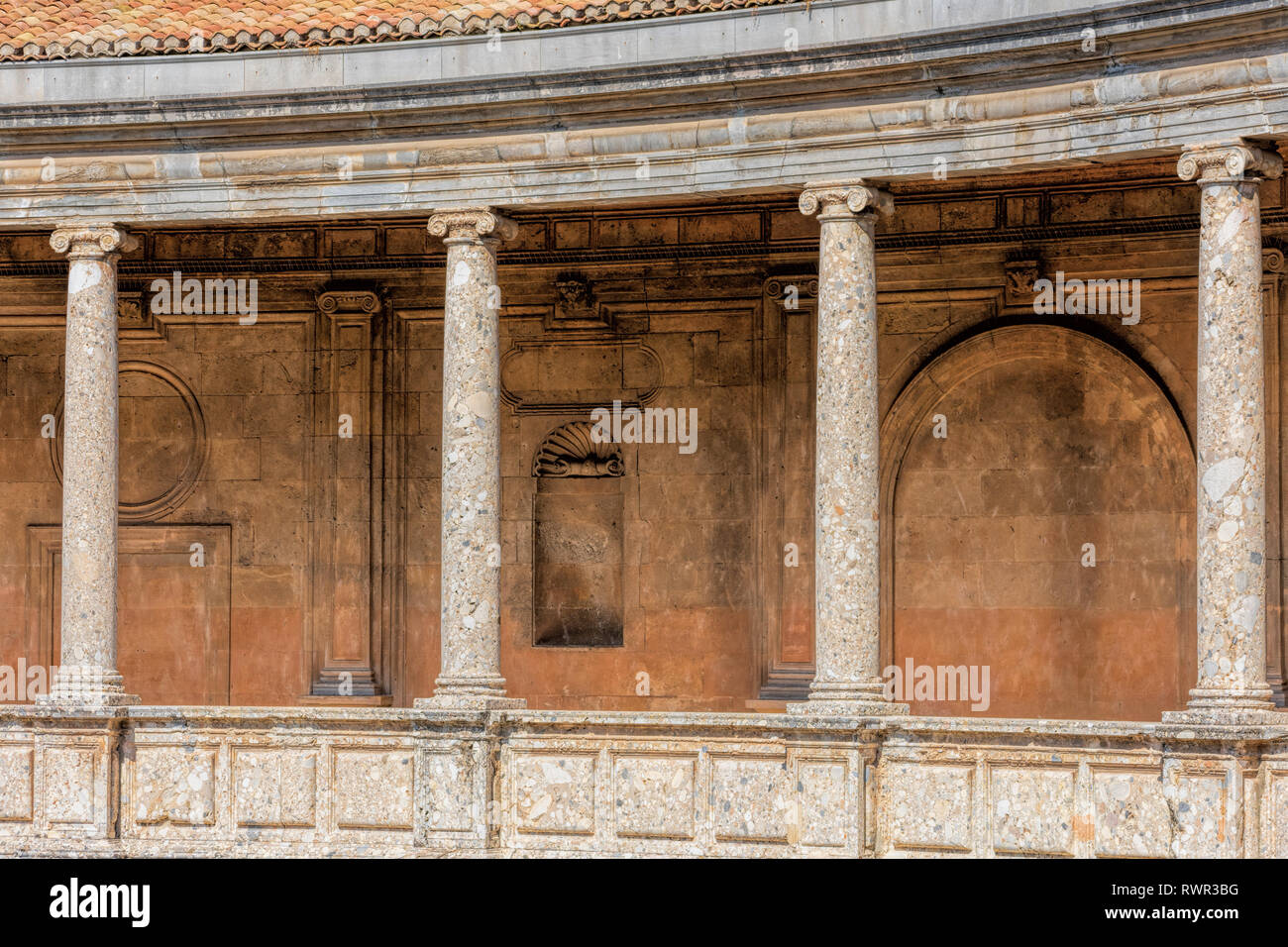 Stylized ionic colonnade whose entablature has no decoration on the upper floor of Palace of Charles V inside the Nasrid fortification of the Alhambra - Stock Image