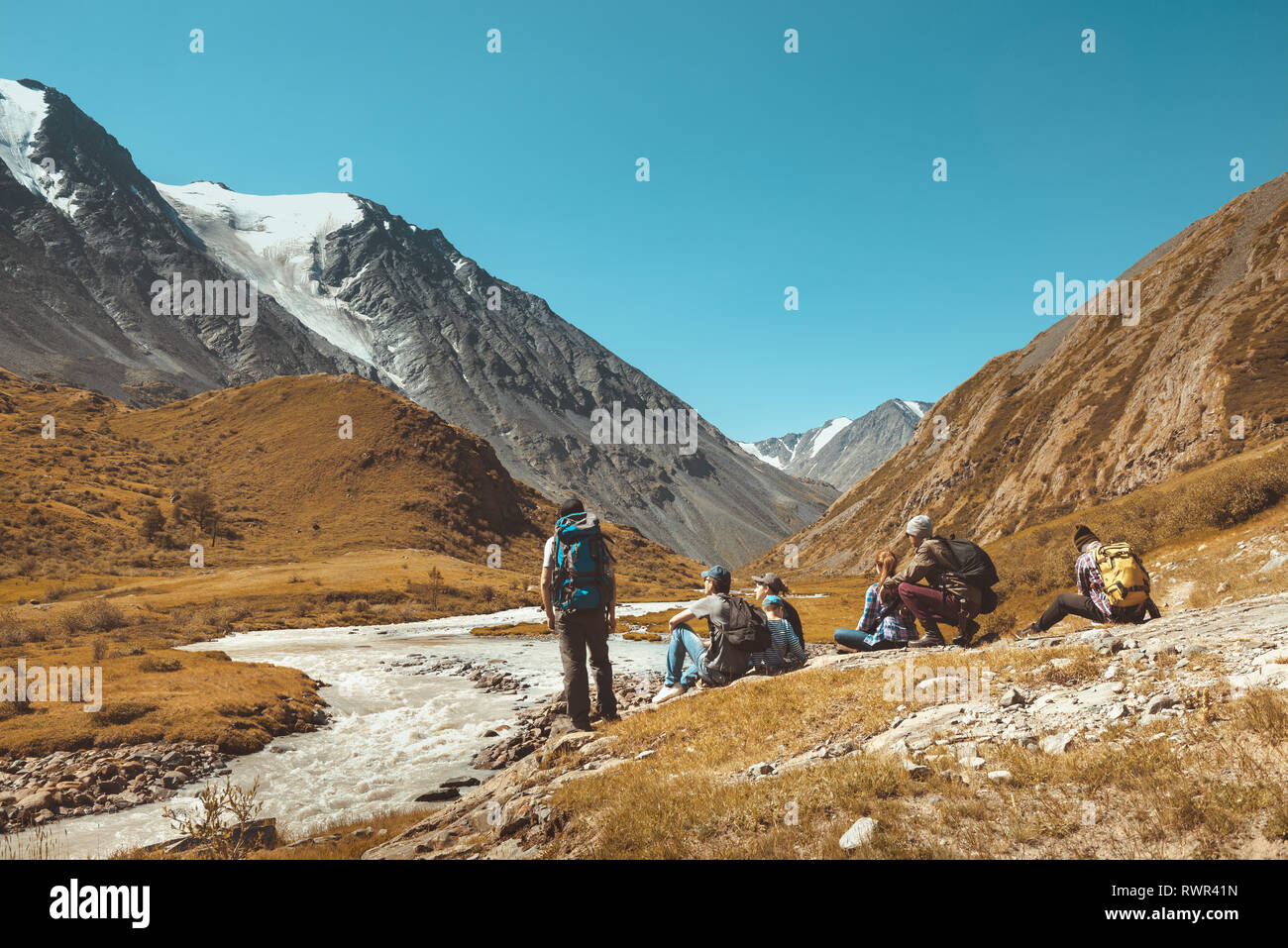 Big group of hikers having rest against mountains and river. Space for text Stock Photo