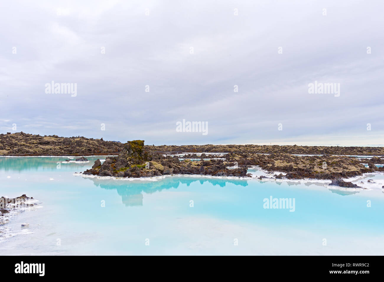A lava field with geothermal water near Grindavik in Iceland. Beautiful unearthly landscape on a cloudy day. - Stock Image
