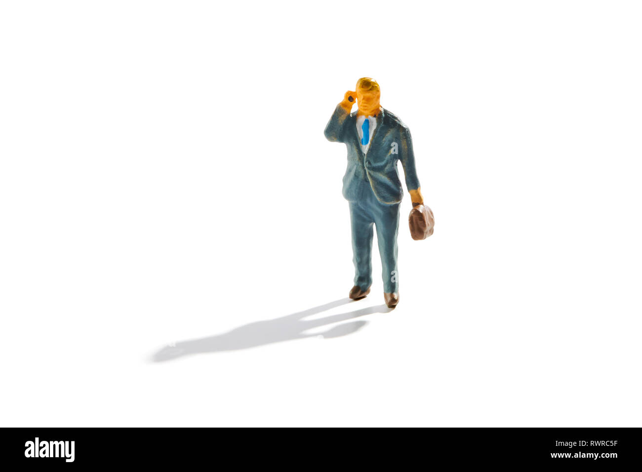 Miniature businessman with briefcase using a mobile phone having a conversation as he walks along with shadow on white - Stock Image