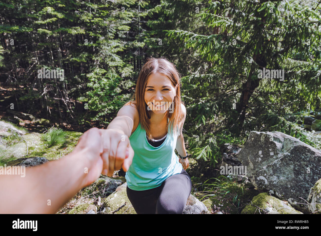 Young woman climbs mountain with help from boyfriend, surrounded by forest - Stock Image