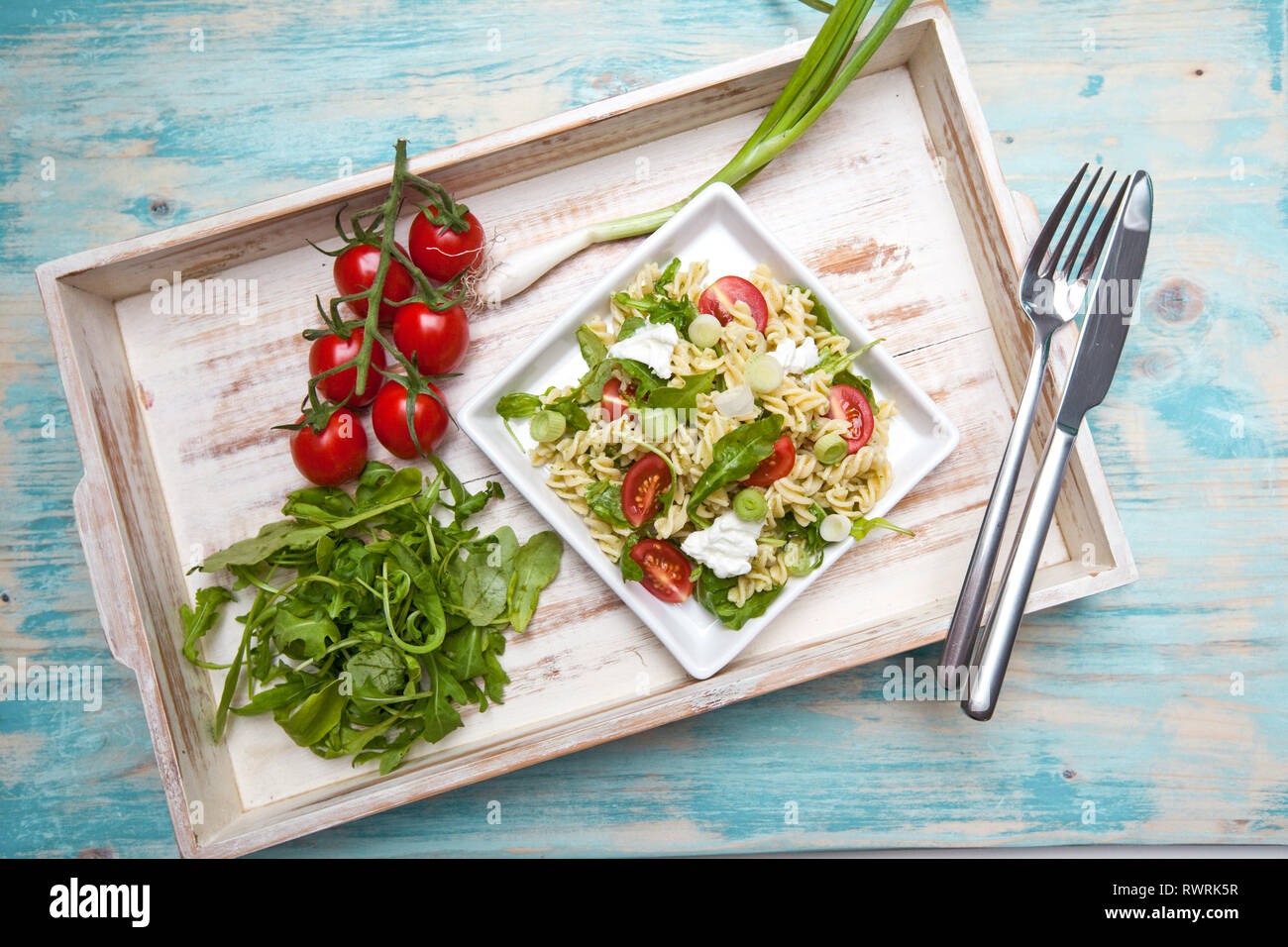 Pasta with mozarella cheese, arugula and vegetables on a wood background Stock Photo