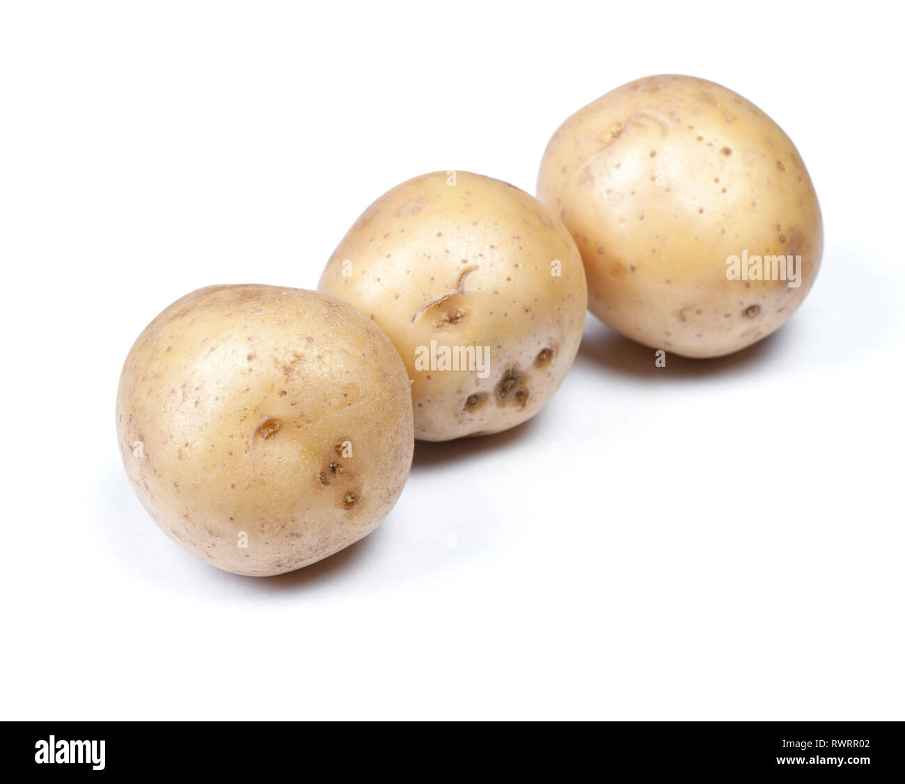 Heap of flawed natural potatoes isolated on white background - Stock Image