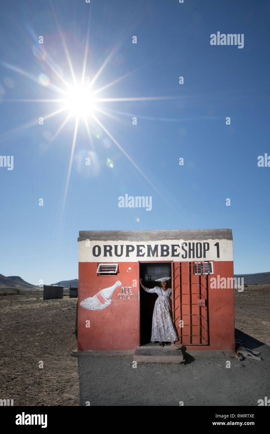 A Herero woman by a shop in the arid Kunene Region of northern Namibia. - Stock Image