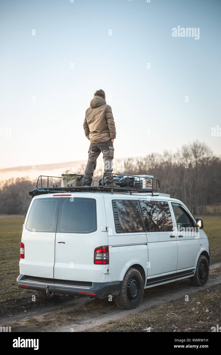 Young man standing on the roof of a van surrounded by nature Stock Photo