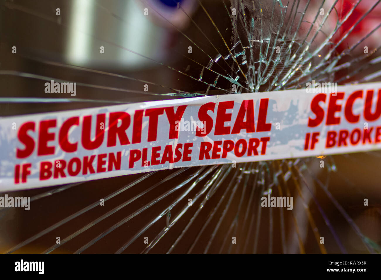 Police Security Seal tape across broken glass window - Stock Image
