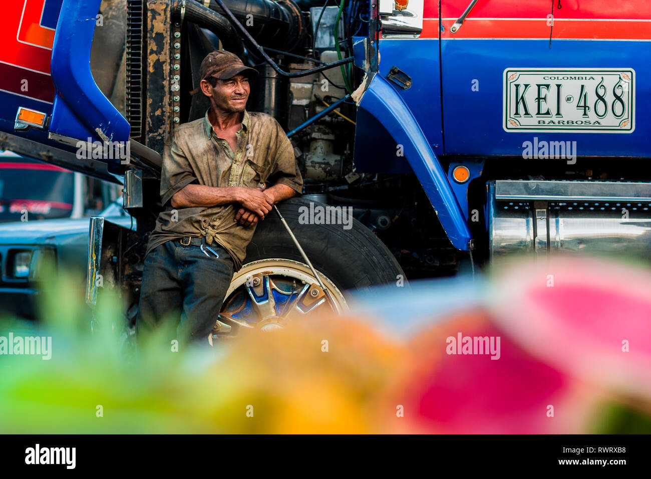 A Colombian car mechanic, leant against the truck wheel, watches the street in Barrio Triste, Medellín, Colombia. - Stock Image