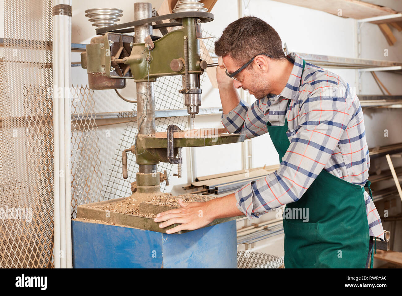 Man as a carpenter works on a drill in the carpentry workshop - Stock Image