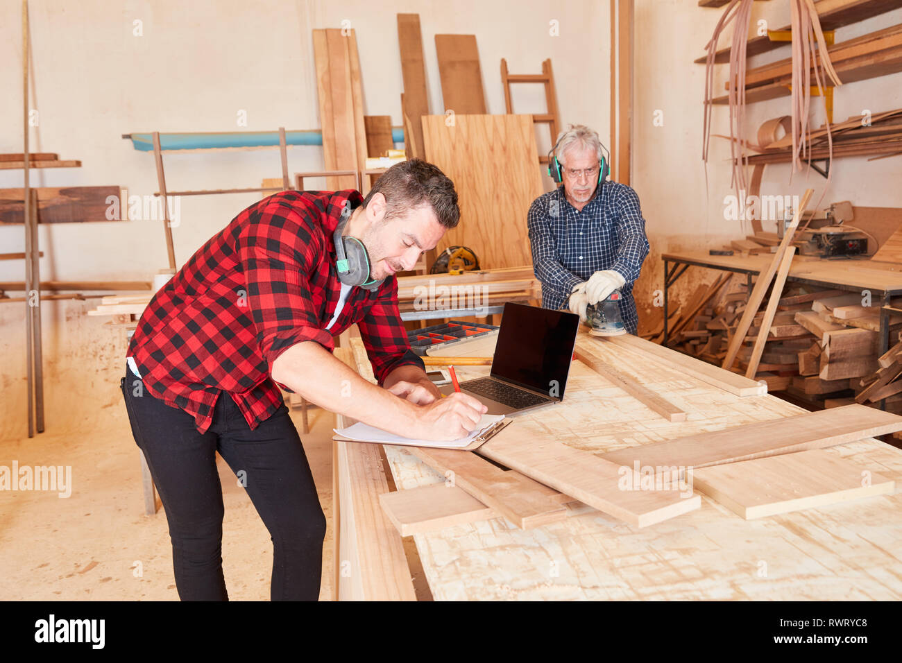 Carpenter with laptop computer and checklist at scheduling in the workshop - Stock Image