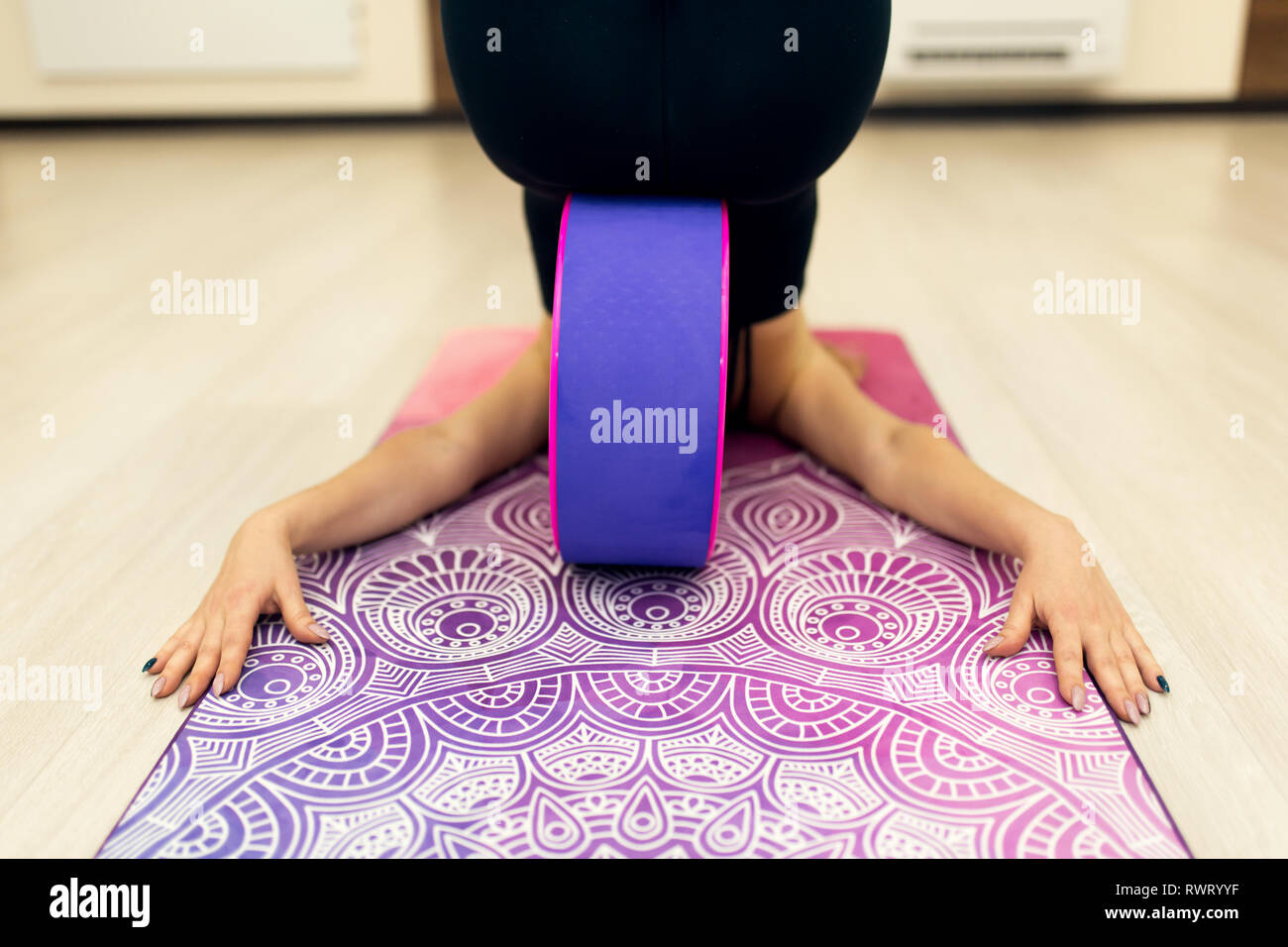 young woman in a sportswear yoga exercises with a yoga wheel in the gym. Stretching and wellness lifestyle. - Stock Image