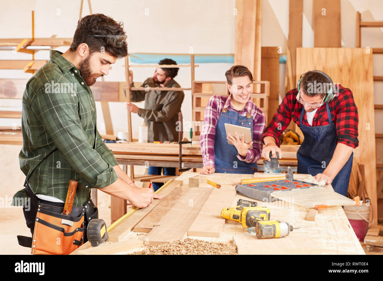 Joiner apprentices in training at the workbench in the carpentry workshop - Stock Image