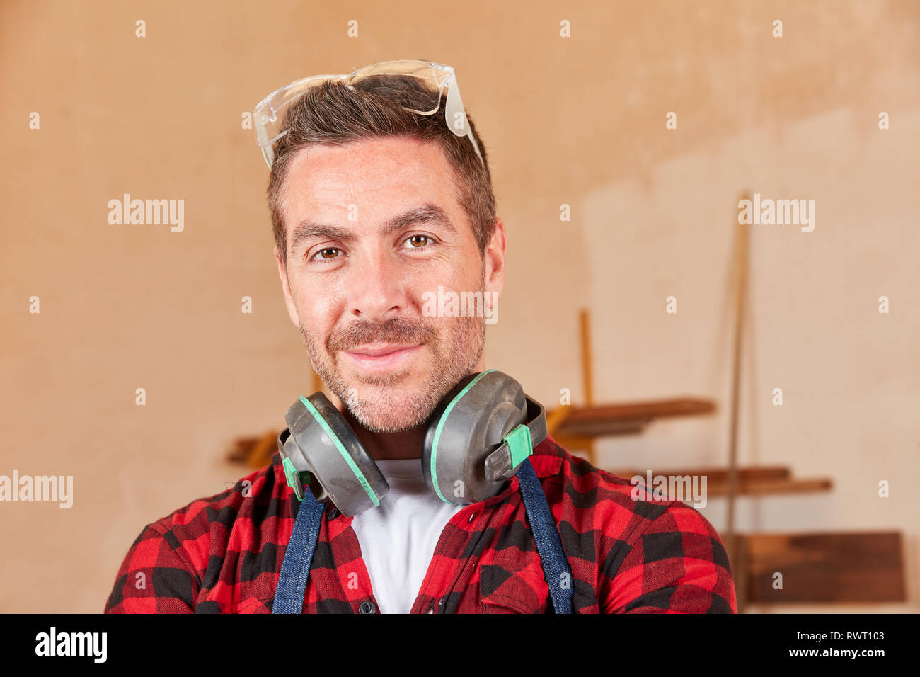 Young man as a worker or joiner apprentice with hearing protection and goggles - Stock Image