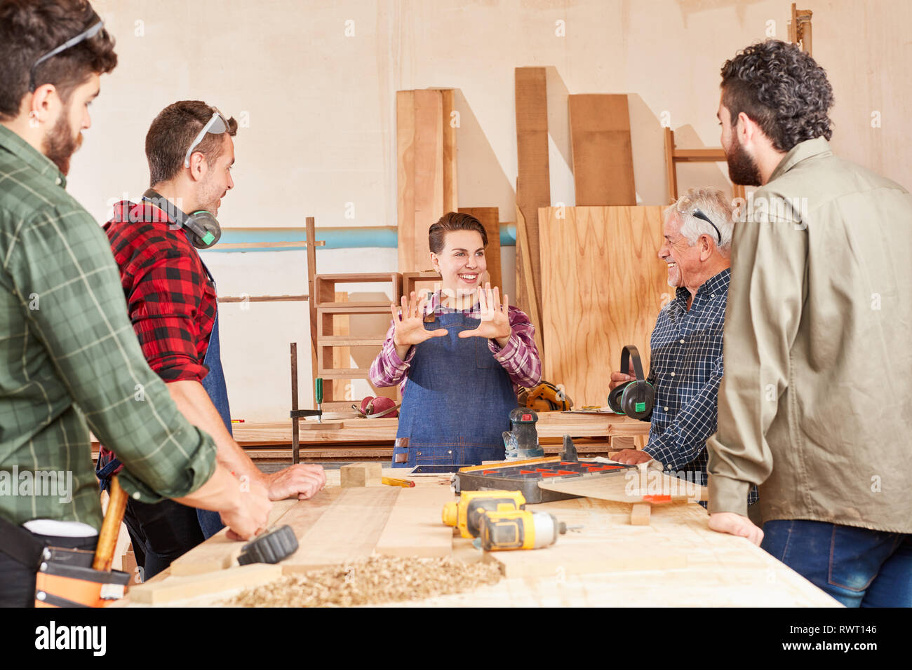 Artisan team and young apprentice woman in teaching together at the workbench - Stock Image