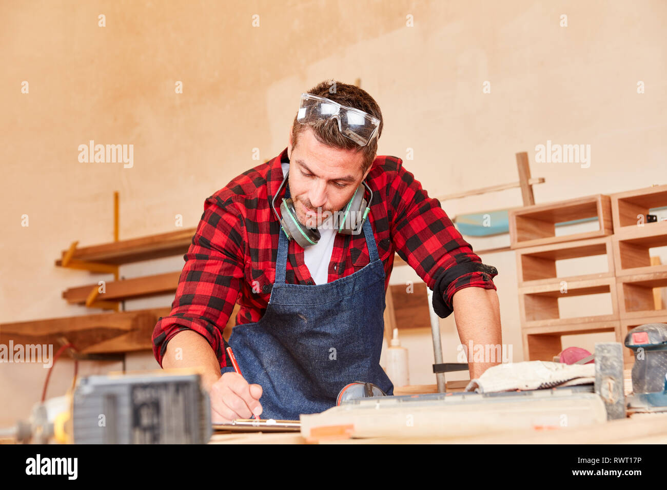 Young man as a carpenter or carpenter with checklist while scheduling - Stock Image