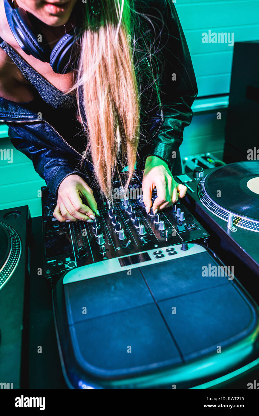 cropped view of dj girl touching equalizer on dj mixer in