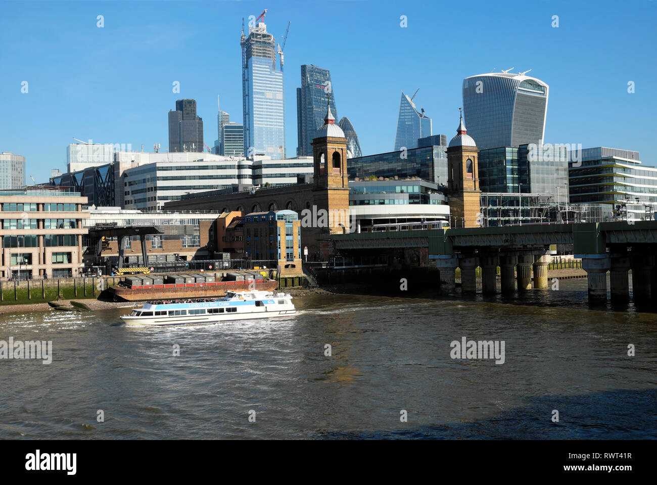Tourist boat on the River Thames & view of Cannon Street Station & buildings in the City of London UK  KATHY DEWITT - Stock Image