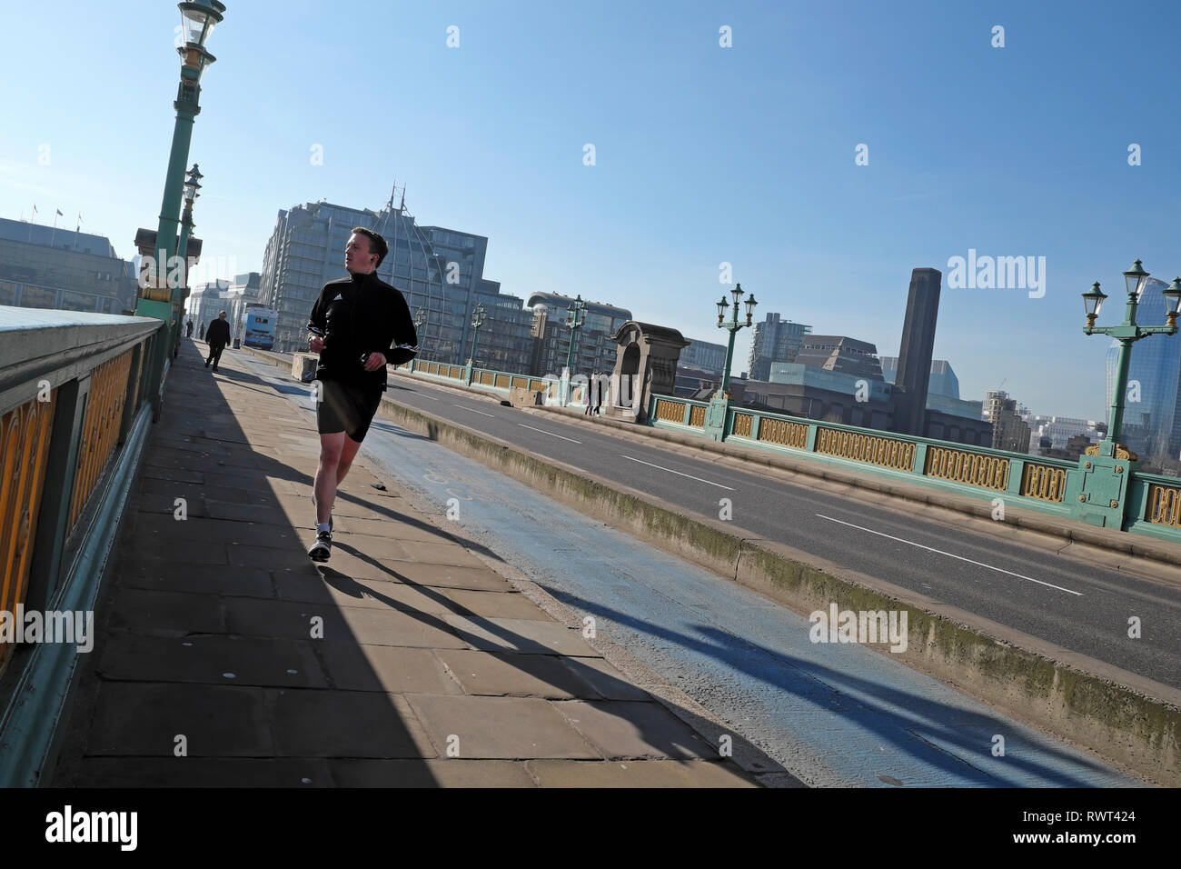 Man in lycra running across Southwark Bridge with a view of the Tate Modern building on a sunny winter day in City of London England UK  KATHY DEWITT - Stock Image