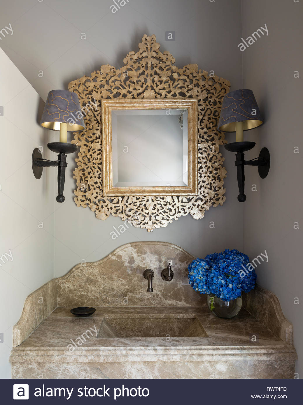 Gold mirror over bathroom sink - Stock Image