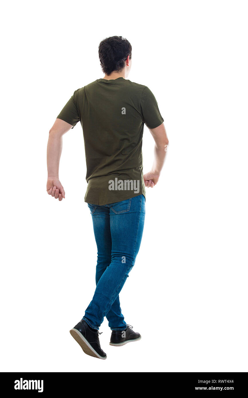 Full length rear view of casual young man confident fast walking isolated over white background. Motion shot making a step going ahead hurried. Stock Photo